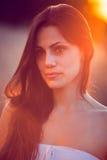 Härlig flicka i vetefält på solnedgången Royaltyfri Fotografi