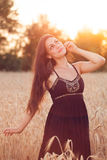 Härlig flicka i vetefält på solnedgången Arkivfoton