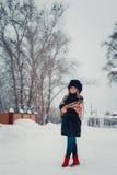 Härlig flicka i vinterkläder, lag och hatt som poserar nära Arkivfoto