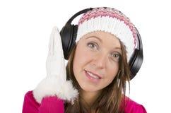 Härlig flicka i vinterkläder med hörlurar som lyssnar till musik arkivbilder
