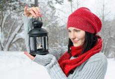 Härlig flicka i vinterskog med lyktan Arkivfoto