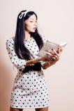 Härlig flicka i vit klänningläsning för prick royaltyfri foto