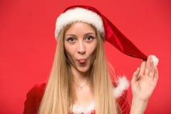 Härlig flicka iklädda Santa Claus över en röd bakgrund arkivbild