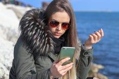 härlig flicka Lycklig kvinna som ser till telefonen på stranden med havet i bakgrunden arkivbild