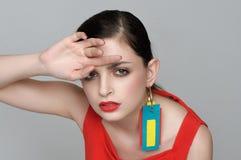Härlig flicka med örhängen i form av etiketter på kläder Royaltyfria Bilder