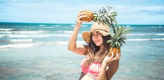 Härlig flicka med ananas på en exotisk strand, ett lyckligt lynne a Royaltyfri Fotografi