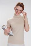 Härlig flicka med böcker och bärande exponeringsglas Royaltyfri Foto