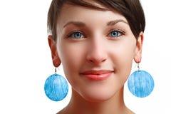 Härlig flicka med blåa ögon och örhängen Royaltyfria Bilder