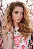 Härlig flicka med blont hår i elegant kläder som poserar i bloo royaltyfri foto
