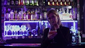 Härlig flicka med blont hår som står nära stångräknaren på bakgrunden av flimrande ljus i en nattklubb gulligt stock video
