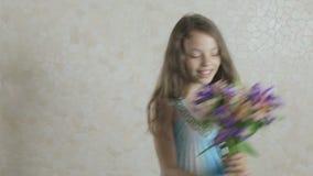 Härlig flicka med buketten av att skratta för blommor lager videofilmer