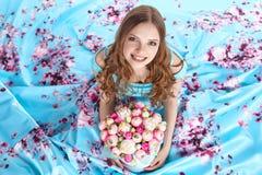 Härlig flicka med buketten av blommor som sitter på golvet Royaltyfri Foto