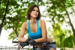 Härlig flicka med cykeln Arkivfoto