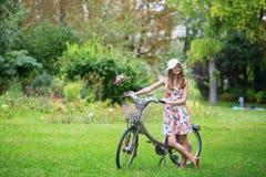 Härlig flicka med cykeln i bygden Royaltyfria Bilder