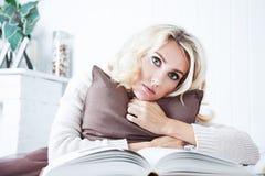 Härlig flicka med den öppna boken och kudden krama kuddekvinnabarn Begrepp av förhållandet Arkivfoto
