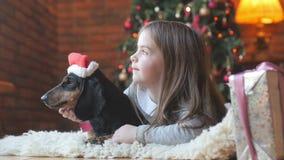 Härlig flicka med den favorit- hunden för sowai i det Santa Claus locket arkivfilmer