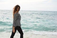 Härlig flicka med den randiga skjortan som går på stranden Royaltyfri Fotografi