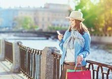 Härlig flicka med den shoppingpåsar och mobiltelefonen Royaltyfri Fotografi