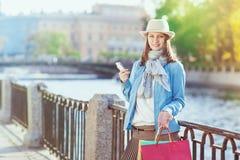 Härlig flicka med den shoppingpåsar och mobiltelefonen Arkivfoto