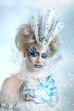 Härlig flicka med det idérika sminket för det nya året Barn härlig kvinna som blåser snow in mot kamera på vinterbakgrund Arkivfoton