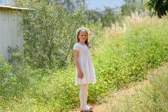 Härlig flicka med det vita klänninganseendet på en härlig bana på solnedgången arkivbild