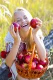 Härlig flicka med en korg av äpplen Fotografering för Bildbyråer