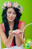 Härlig flicka med en korg av påskägg I Arkivfoton
