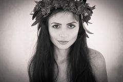Härlig flicka med en krans av blommor på hennes huvud Royaltyfria Bilder