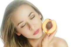 Härlig flicka med en persika och stängda ögon Arkivbilder