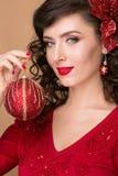 Härlig flicka med en röd julboll Arkivfoto