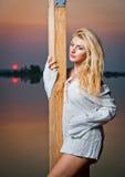 Härlig flicka med en vit skjorta på pir på solnedgången Royaltyfri Bild