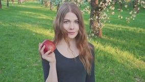 Härlig flicka med ett äpple i hennes händer mot bakgrunden av en äpplefruktträdgård En kvinna önskar att äta ett äpple lager videofilmer