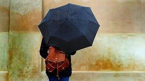 Härlig flicka med ett brunt paraply för läderryggsäckinnehav i gatan på en regnig dag - besöka Copenaghen arkivfoto