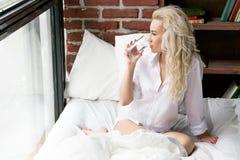 Härlig flicka med ett exponeringsglas av vatten i säng Royaltyfri Fotografi