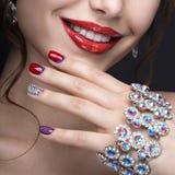Härlig flicka med ett ljust aftonsmink och röd manikyr med bergkristaller Spika designen Härlig le flicka royaltyfria foton