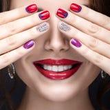 Härlig flicka med ett ljust aftonsmink och röd manikyr med bergkristaller Spika designen Härlig le flicka Arkivbilder