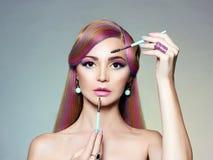Härlig flicka med färgrikt hår som applicerar smink arkivfoto