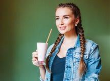 Härlig flicka med flätade trådar som sitter i ett kafé och dricker en milkshake som ut ser fönstret Arkivfoton