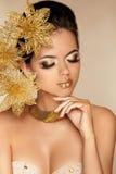 Härlig flicka med guld- blommor.   Arkivbilder