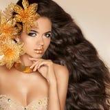 Härlig flicka med guld- blommor Skönhetmodell Woman Face per Arkivbild