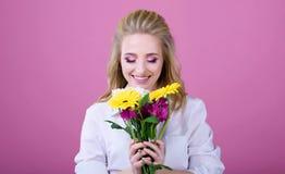 Härlig flicka med härliga blommor på en rosa bakgrund royaltyfria foton
