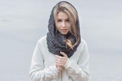 Härlig flicka med härliga kanter i ett vitt omslag med en varm halsduk på huvudet i kallt väder royaltyfria bilder