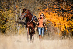 Härlig flicka med hästen i höstskog Arkivfoto