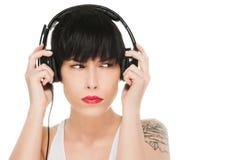 Härlig flicka med hörlurar som isoleras på vit Arkivfoto