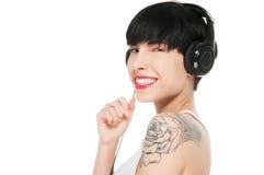 Härlig flicka med hörlurar som isoleras på vit Arkivfoton
