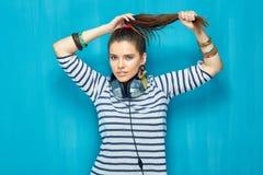 Härlig flicka med hörlurar, svanshårstil arkivbild
