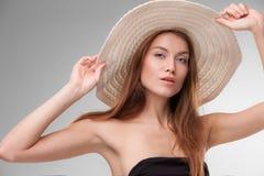 Härlig flicka med hatten som poserar i studio Fotografering för Bildbyråer