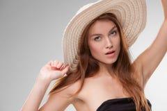 Härlig flicka med hatten som poserar i studio Arkivbilder