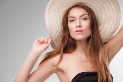 Härlig flicka med hatten som poserar i studio Arkivfoto