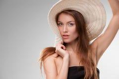 Härlig flicka med hatten som poserar i studio Arkivbild